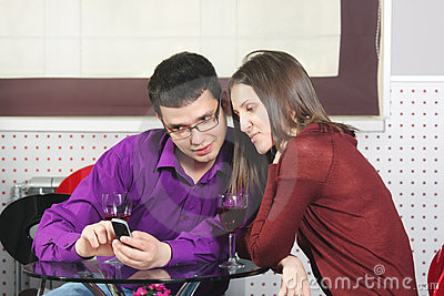 Couple in cafe looking at cellphone
