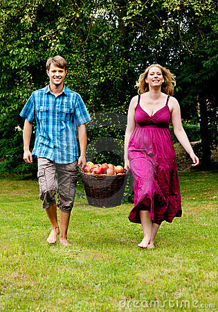 Couple carrying basket with apples