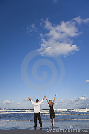Couple Celebrating Arms Raised On A Beach