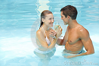 Couple celebrating with sparkling wine in pool