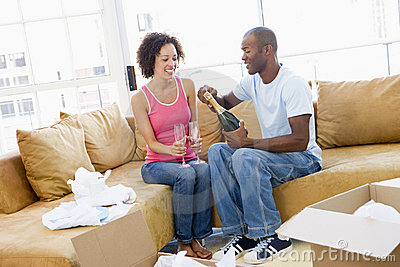 Couple with champagne by boxes in new home