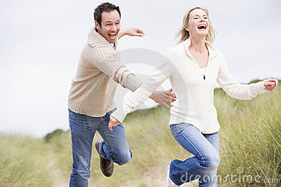 Couple chasing one another through dunes