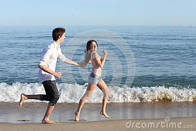 Couple chasing and running on the beach shore