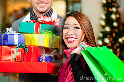 Couple Christmas shopping with presents in mall