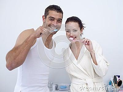 Couple cleaning their teeth in bathroom