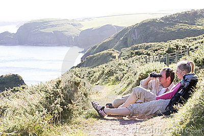 Couple on cliffside outdoors using binoculars