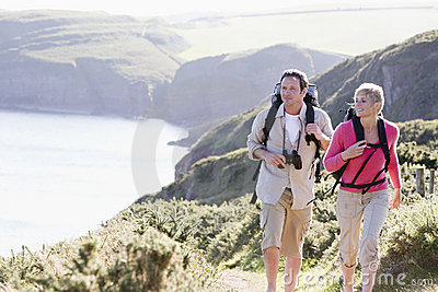 Couple on cliffside outdoors walking and smiling