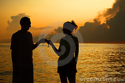 Couple clink glasses. Silhouettes against sea