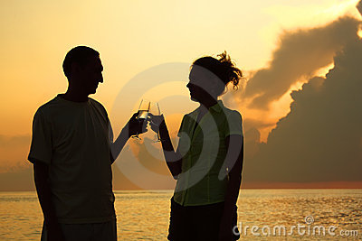 Couple clink glasses. Silhouettes against sea.
