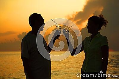 Couple clink glasses. Splashes of wine.