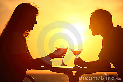 Couple clink glasses on sunset outside