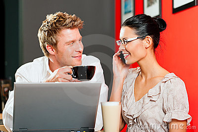 Couple in coffeeshop with laptop and mobile