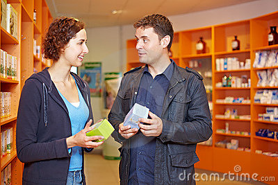 Couple comparing drugs in pharmacy