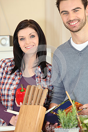 Couple cooking meal from recipe