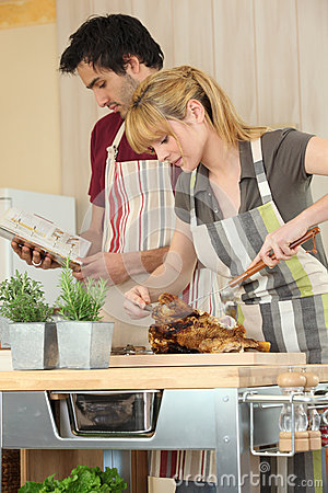Couple cooking roast chicken