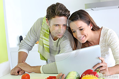 Couple cooking and using tablet