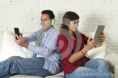 Couple On Couch Ignoring Each Other Using Mobile Phone And ...