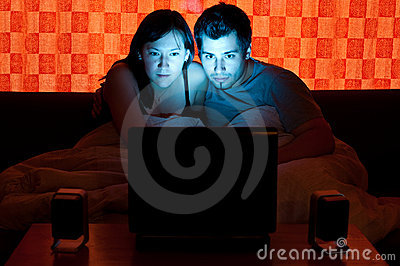 Couple on a couch watching a movie