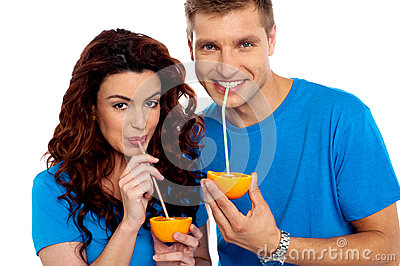 Couple cuddling and sipping orange juice