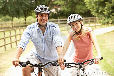 Couple Cycling In Countryside Wearing Safety Helme