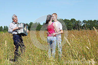 Couple dance near grandfather plays on accordion