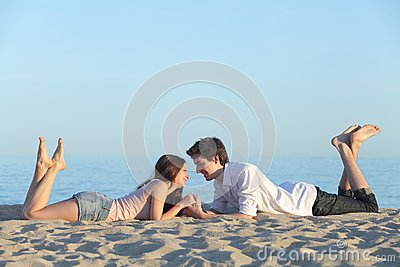 Couple dating and resting on the beach sand