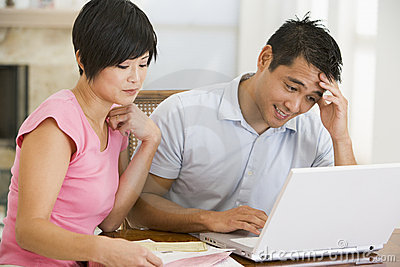 Couple in dining room with laptop looking unhappy