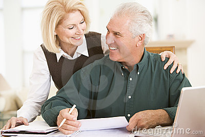 Couple in dining room with laptop and paperwork