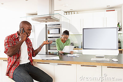 Couple Discussing Personal Finances In Kitchen