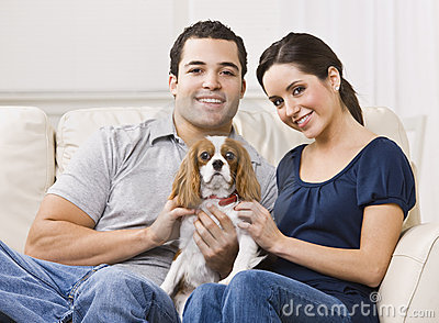 Couple with dog on their lap in their living room.