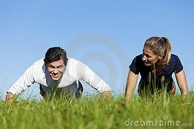 Couple doing push ups in summer grass