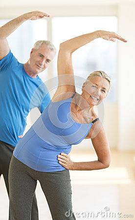 Couple Doing Stretching Exercise At Home