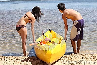 Couple dragging kayak onto lake
