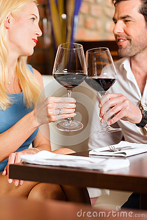 Couple drinking red wine in restaurant or bar