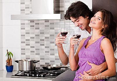 Couple drinking wine in their kitchen