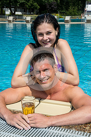 Couple with drinks at swimming pool