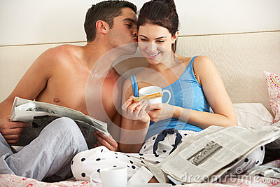 Couple Eating Breakfast And Reading Newspaper In Bed