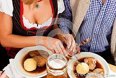 Couple eating roast pork in Bavarian restaurant