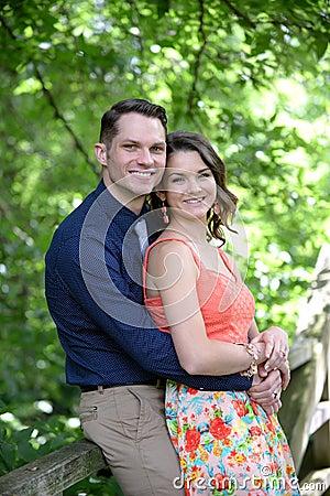 Couple embrace on bridge