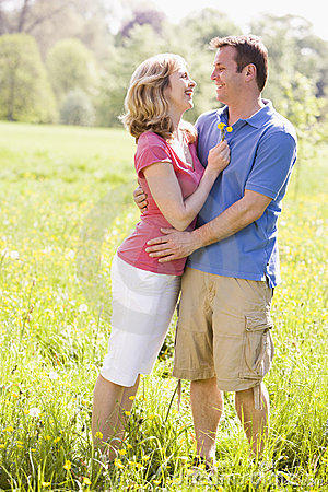 Couple embracing outdoors holding flower smiling