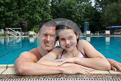 Couple enjoying holidays at pool edge