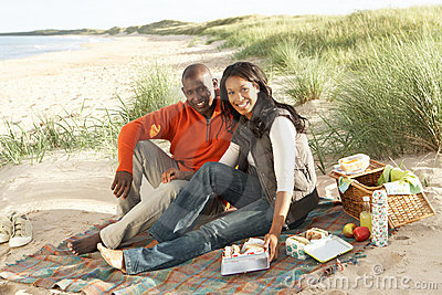 Couple Enjoying Picnic On Beach Together