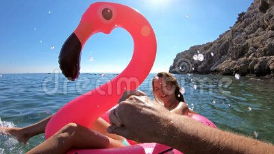 Couple enjoying the sea and the sun on the Mediterran. Floating on an inflatable Flamingo. POV stock footage