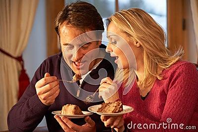 Couple Enjoying Slice Of Cake Sitting On Sofa