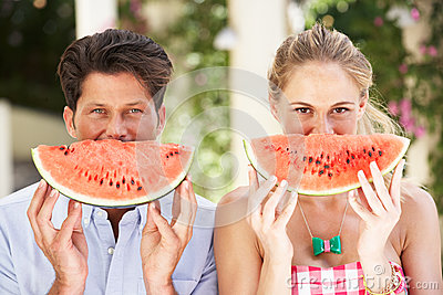 Couple Enjoying Slices Of Water Melon