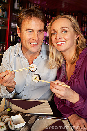 Couple Enjoying Sushi In Restaurant