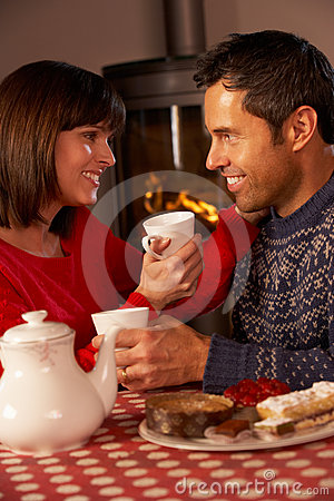 Couple Enjoying Tea And Cake By Cosy Log Fire
