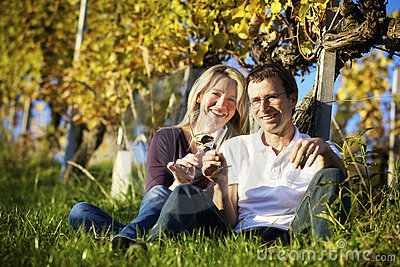 Couple enjoying wine in vineyard.