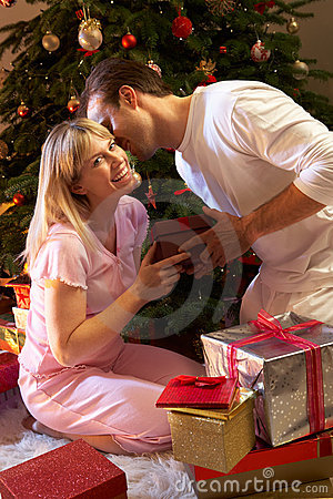 Couple Exchanging Presents In Front Of Tree