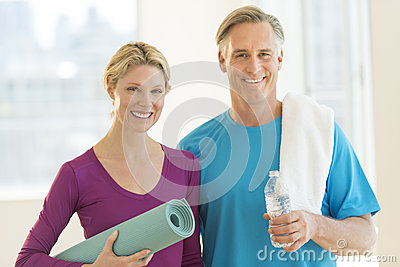 Couple With Exercise Mat; Water Bottle And Towel In Club